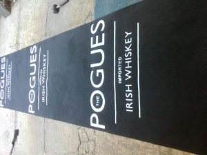 the pogues event or promotional mat with black background and white logo