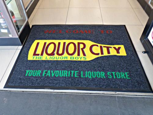 liquor city branded mat with a bright yellow bottle